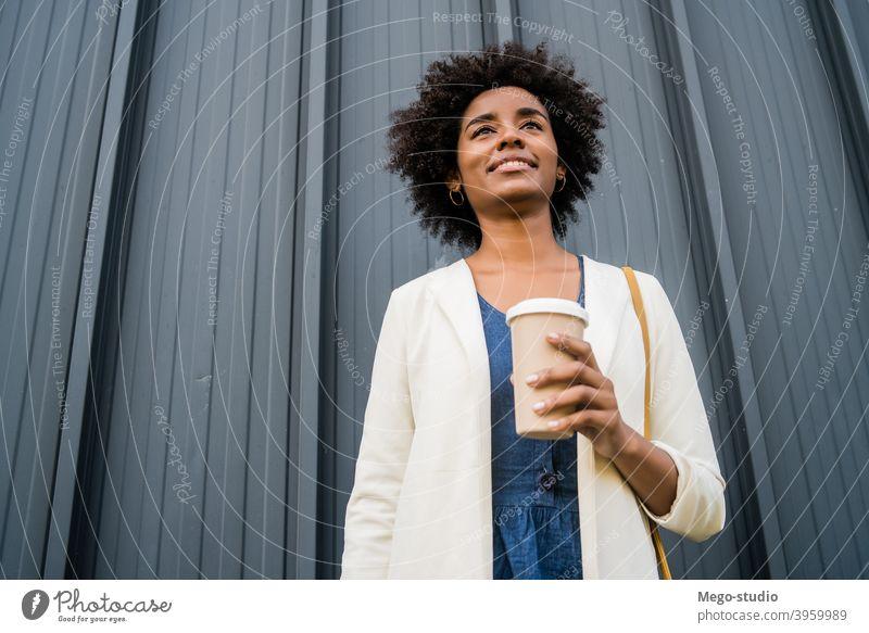 Porträt einer afroamerikanischen Geschäftsfrau im Freien. Afro-Look Business Frau urban Lächeln Erwachsener Kaffee Kaffee zum Mitnehmen Anzug Unternehmen