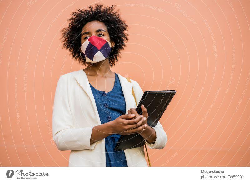 Afro-Geschäftsfrau steht im Freien auf der Straße. Afro-Look Business Frau Schutzmaske Beruf behüten trinken Pandemie Geschäftsmann Konzept Getränk korporativ