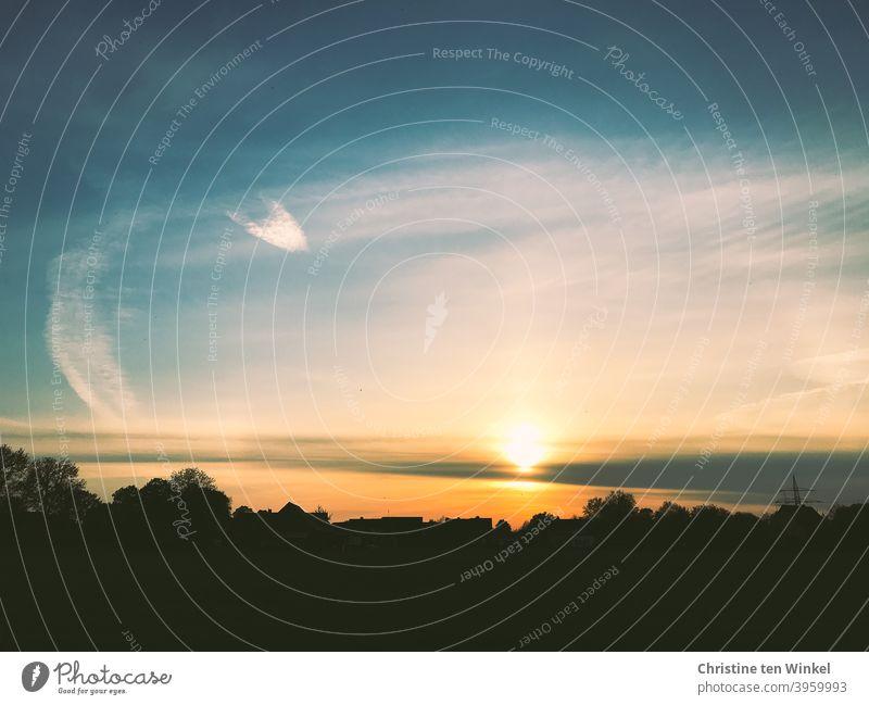 Systemrelevant I Unsere Sonne ... Sonnenuntergangsstimmung  in leuchtenden Farben mit dunklen Silhouetten von Bäumen und Häusern. Schöne und auffällige Wolkenformation