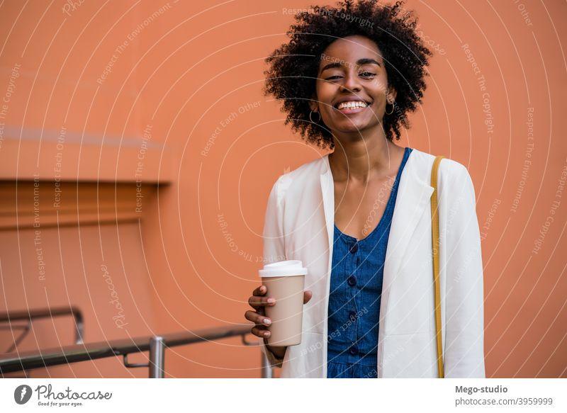 Afro-Geschäftsfrau hält eine Tasse Kaffee im Freien. Afro-Look Business Frau urban Lächeln Erwachsener Kaffee zum Mitnehmen Anzug Unternehmen Geschäftsleute