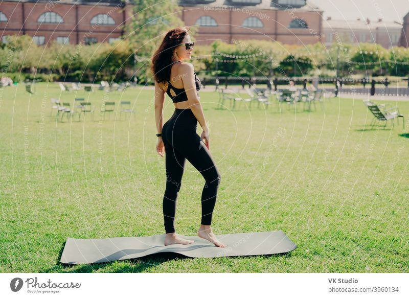 Fit brunette Frau in Sportkleidung gekleidet steht barfuß auf karemat hat fintess Ausbildung auf grünem Rasen im Freien während der Sommerzeit trägt eine Sonnenbrille sieht irgendwo in guter körperlicher Verfassung sein