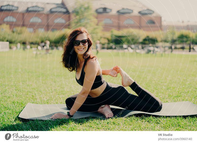 Glücklich fit junge Frau tut Stretching-Training auf Fitness-Matte Praktiken Yoga außerhalb in activewear gekleidet hat starken Körper atmet frische Luft im Freien führt aktiven Lebensstil. Sport Fitness Konzept
