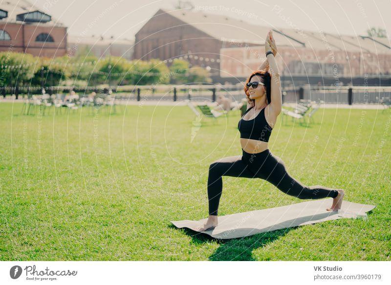 Konzentrierte positive Frau hebt Arme tut Pilates-Übungen in aktive Kleidung Sonnenbrille gekleidet hat Training im Sommer Praktiken Yoga-Posen auf grünem Gras. Menschen und gesunden Lebensstil Konzept