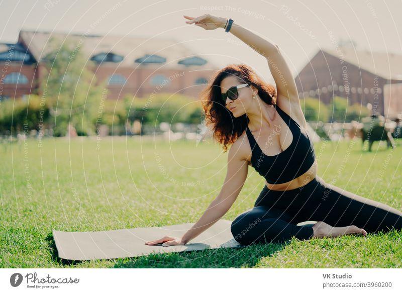 Bild von motivierten fit Frau hebt Arm und macht Dehnübungen im Freien posiert auf Fitness-Matte trägt Sonnenbrille und activewear Züge aktiv. Fitness-Trainer geht in für Sport im Freien