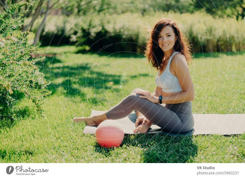 Positive brunette Frau in abgeschnittenen Top und Leggings posiert nackten Füße auf karemat verwendet Ball für gymnastische Übungen lächelt angenehm genießt schöne Natur Blick. Sport im Freien. Yoga-Praxis.