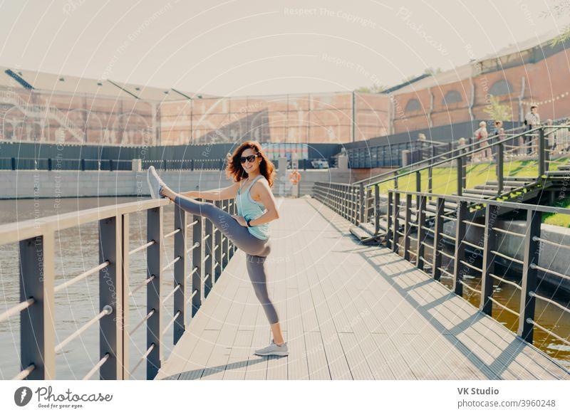Glad brunette Frau lehnt am Zaun streckt Beine hat perfekte Figur gekleidet in activewear Posen im Freien demonstriert ihre Flexibilität führt sportlichen Lebensstil wärmt sich vor Fitness-Training.