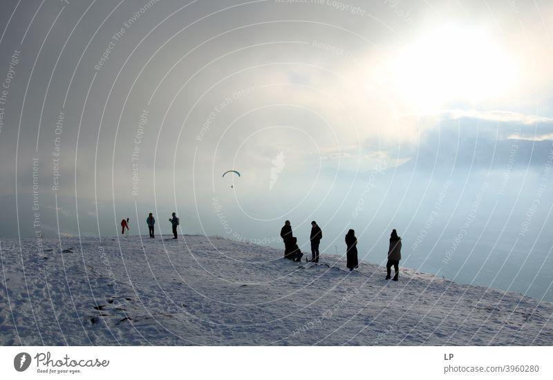 Silhouetten warten auf dem Berg an einem nebligen Tag beobachten einen Paraglider Glaube und Religion betend Gebet Hintergrund weitergeben Zufriedenheit