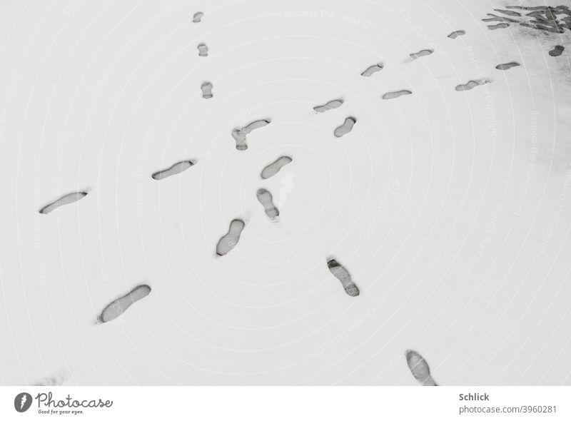 Fußspuren im Schnee kreuzen sich einer ging hin und her gehen auf der Stelle treten Einzelgänger überkreuzen Schneefläche Spuren auf der Stelle stehen Ecke
