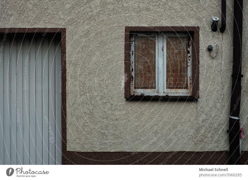 Alte Hauswand mit rostigem Gitterfenster, Wasserrohr und Garage Hauswandfenster Wand Fassade Außenaufnahme Menschenleer Mauer Gebäude Farbfoto trist Stadt