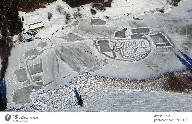 Luftaufnahme mit einer Drohne von einem zugefrorenen See im Winter mit Schlittschuhläufern luftaufnahme drohnenfoto see eis eislaufen wintersport schnee