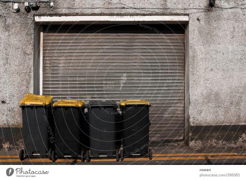 NCH | muelltonnen Fassade dreckig Müll Müllbehälter Müllabfuhr gelb Garage Garagentor schäbig geschlossen Reihe Recycling Farbfoto Gedeckte Farben Außenaufnahme