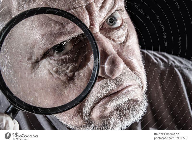 ein Mann schaut skeptisch durch eine große Lupe Porträt sehen schauen beobachten Gesicht Blick Auge Mensch Farbfoto Blick in die Kamera Erwachsene Kopf Neugier