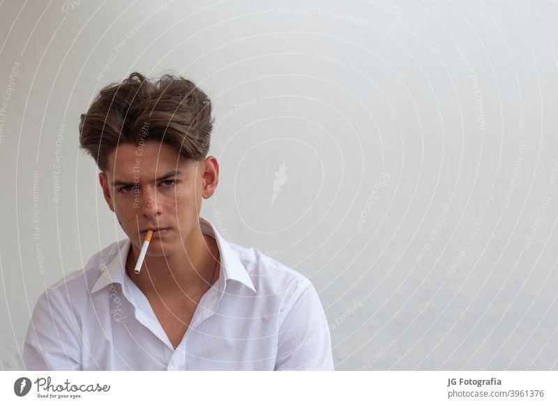 Junger Mann mit Zigarette im Mund schaut in die Kamera mit grauem Wandhintergrund. jung Typ Rauchen Porträt Blick schädlich Krebs Aussehen Model sommersprossig