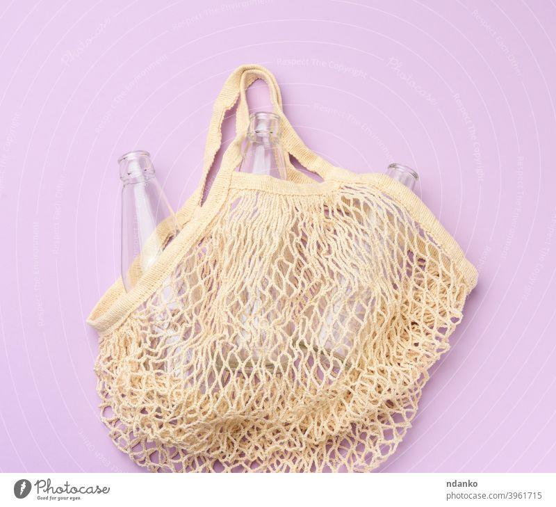 wiederverwendbare Textil-Einkaufstasche mit leeren Flaschen auf einem lila Hintergrund Glas purpur Lebensmittelgeschäft Handtasche Lifestyle Markt Netzbeutel