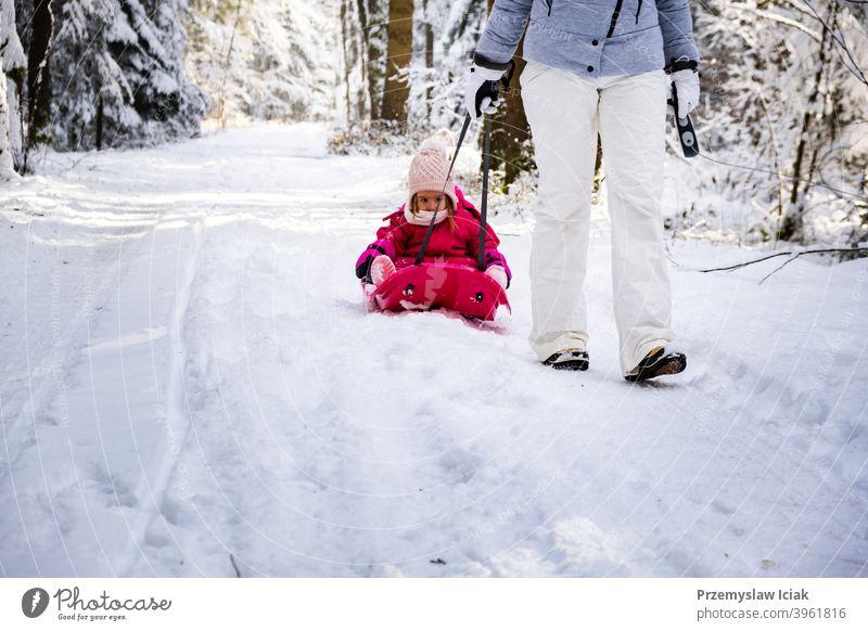 Mutter, die ihr Baby auf einem Schlitten durch den Winterwald zieht. Hintergrund offen Wald Familie authentisch ziehend Kind Person Mädchen Weihnachten Natur