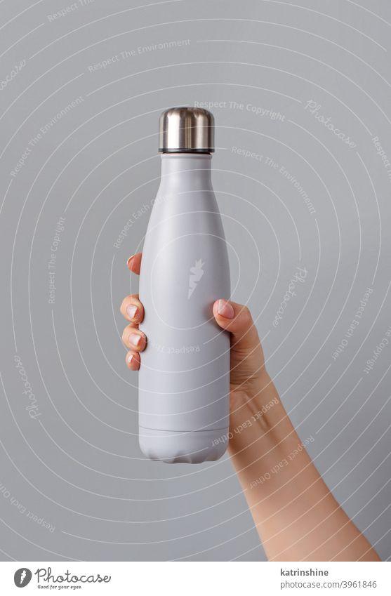 Nahaufnahme einer weiblichen Hand, die eine graue wiederverwendbare Flasche auf grauem Hintergrund hält Frau Monochrom Attrappe gelb isoliert ökologisch Wasser
