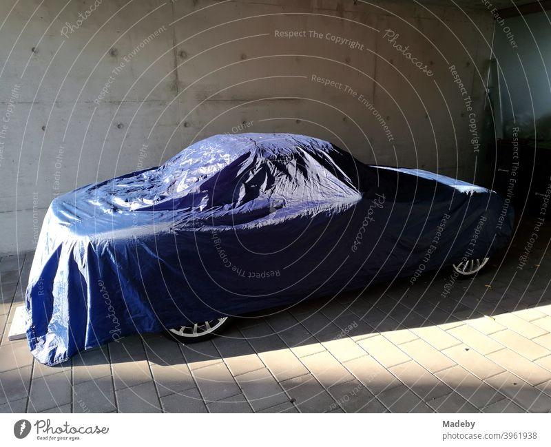 Sportwagen Cabriolet abgedeckt mit einer blauen Plane aus Kunststoff bei Sonnenschein in einem modernen Carport aus Beton Auto Roadster Ebene Schutzhülle