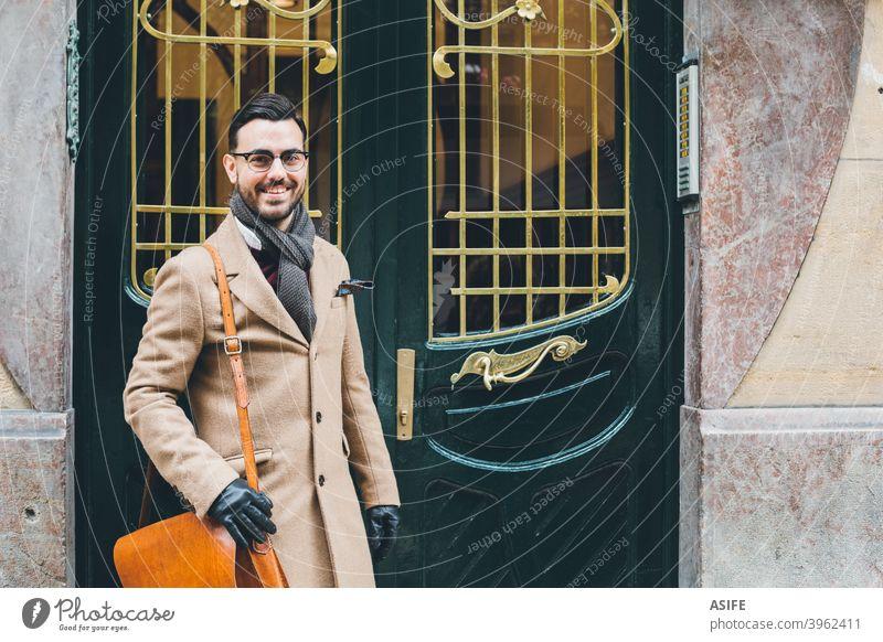 Junge elegante bussiness Mann in einem Retro-Stil Mode an der Haustür jung Schönling Straße Porträt attraktiv modern retro Winter Kavalier bärtig klug Business
