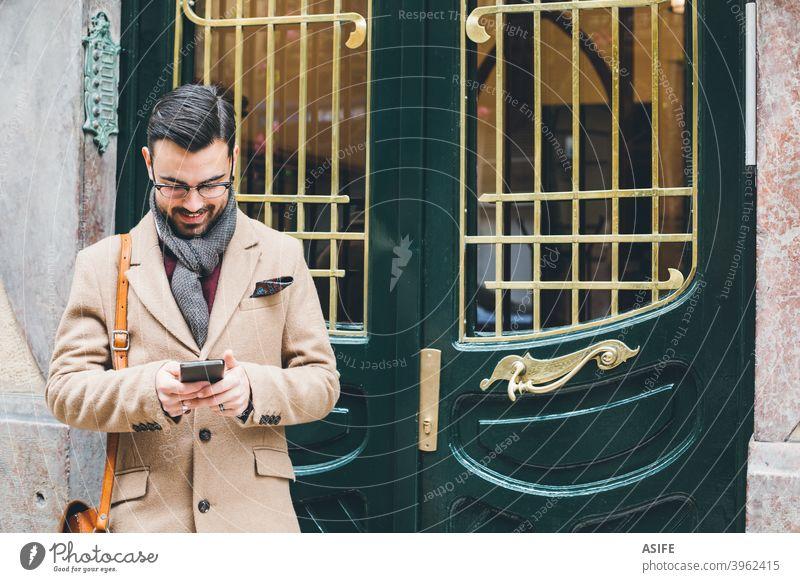 Junger eleganter Mann im Retrostil, der sein Smartphone an der Haustür benutzt jung Schönling Telefon Handy Mobile Stil Mode Straße Porträt