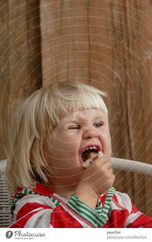 Mh lecker Brot Mädchen süß Freude Grimasse Verschmitzt ponyfrisur Porträt blond kleines Mädchen Kind Kindheit niedlich frech Essen genießen aufgeregt fasziniert