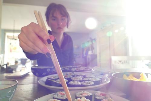 Junge Frau isst vegetarisches, selbstgemachtes Sushi, mit Stäbchen, Lichteinfall von rechts. Japanisch rollen Reis asiatisch traditionell Wasabi Ingwer