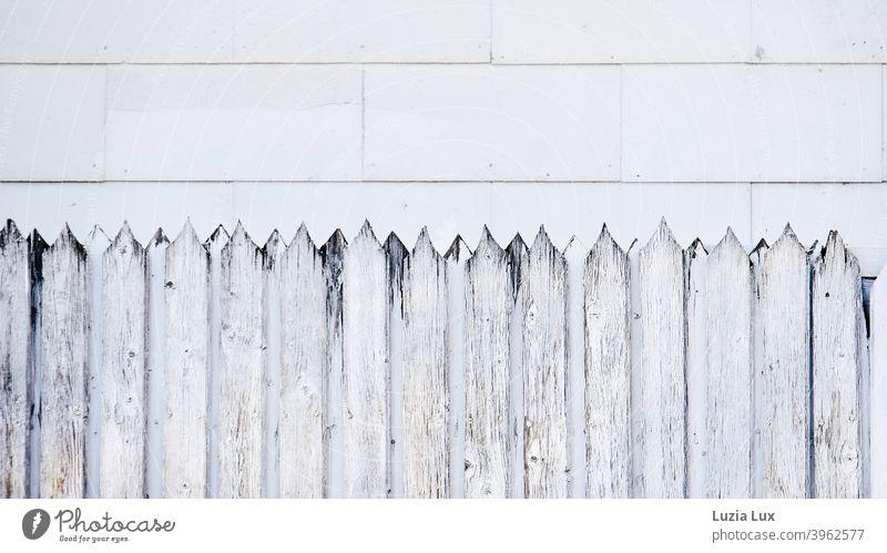 Fassade und Formen, ein alter Holzzaun mit scharfen Zacken vor Fassadenplatten, an denen ebenfalls der Zahn der Zeit genagt hat Zaun Zaunpfähle streng zackig