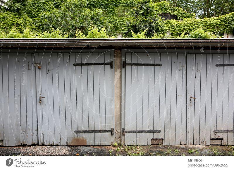 Schuppen Tor Garage Garagentor geschlossen Tür grau trist Hinterhof Gebäude Holztor ruhig Efeu geheimnisvoll Nostalgie verwittert dach garagentor freihalten