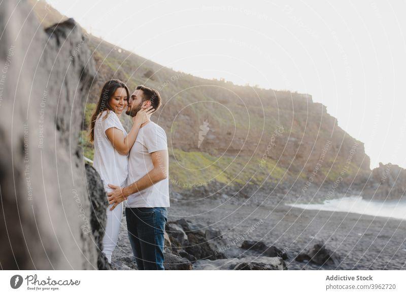 Liebendes Paar, das sich am felsigen Meeresufer umarmt MEER romantisch Umarmen Kuss Küste Strand Zusammensein Zuneigung Glück jung Teneriffa Insel Kanarienvogel