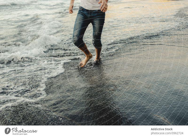 Mann geht entlang nassen sandigen Meeresufer MEER Strand winken Barfuß Reisender Sand Küste Ufer männlich Sonnenuntergang Urlaub Lifestyle Spaziergang reisen