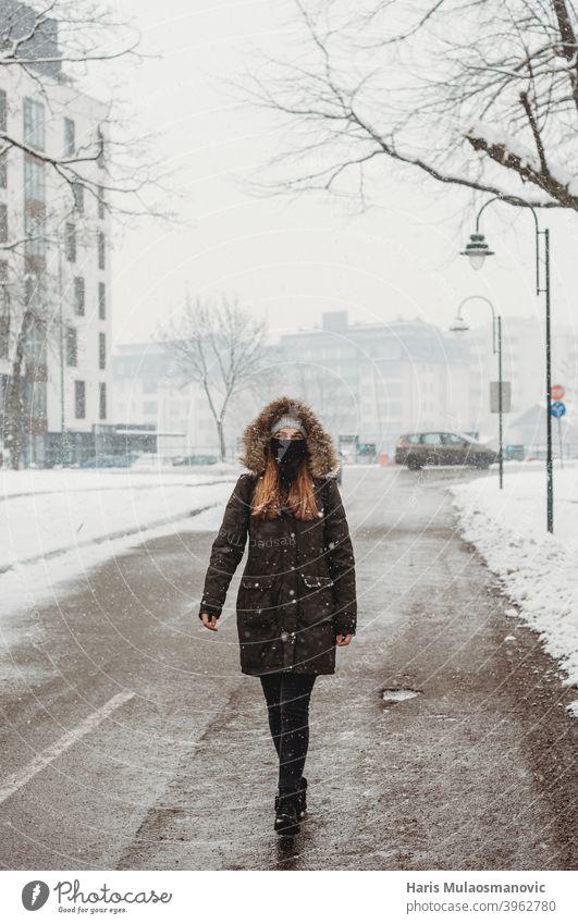 Frau mit Gesichtsmaske geht im Freien im Schnee Erwachsener allein attraktiv schön schwarz brünett kalt selbstbewusst Coronavirus covid-19 niedlich leer
