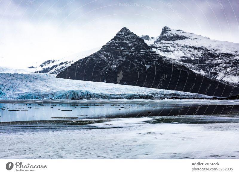 Bergsee im Winter unter grauem Himmel Berge u. Gebirge See Hochland Landschaft Teich Schnee Wasser Windstille Island wolkig malerisch Natur felsig kalt Kamm