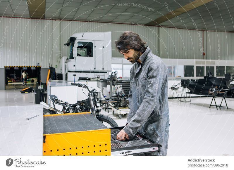 Männlicher Mechaniker in der Nähe von Werkzeugschrank in der Werkstatt Kabinett Mann Arbeit Instrument Motorrad Arbeitsbekleidung männlich geräumig Garage