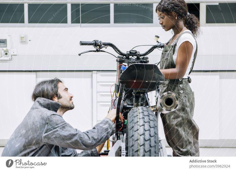 Multiethnische Mechaniker arbeiten gemeinsam in einer Motorradwerkstatt fixieren Zusammensein Kollege Werkstatt Reparatur Werkzeug Dienst multiethnisch