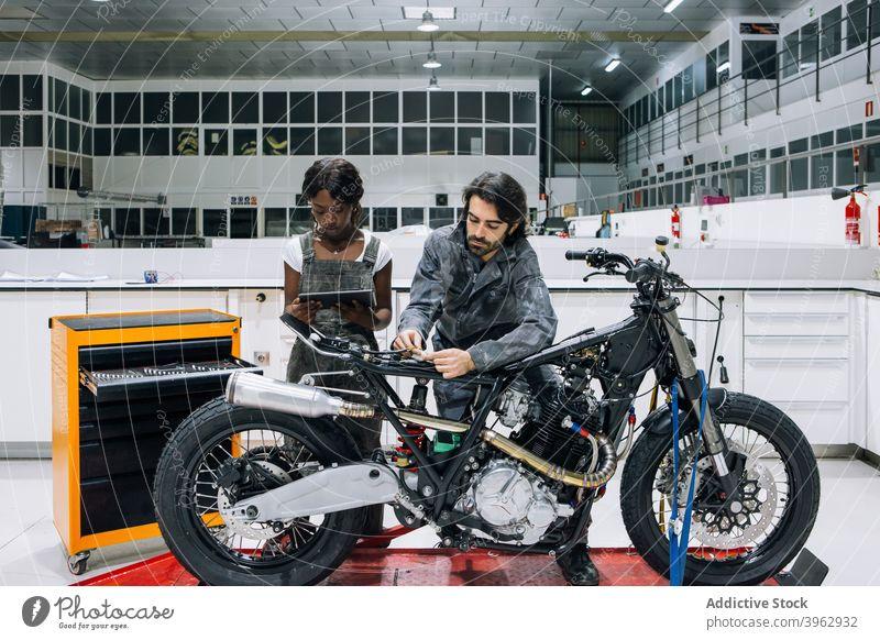 Multiethnische Kollegen arbeiten gemeinsam in der Motorradwerkstatt Werkstatt Mechaniker Zusammensein Arbeit fixieren Tablette Reparatur multiethnisch