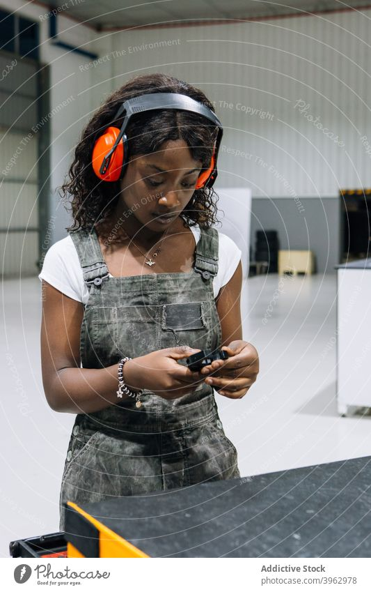 Schwarzer weiblicher Mechaniker wählt Werkzeuge für Reparaturservice Frau Werkstatt professionell wählen Arbeit mechanisch Kopfhörer Sicherheit behüten
