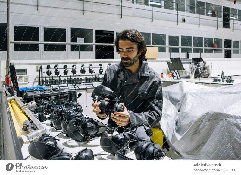 Mechaniker mit Kopfhörer in der Werkstatt Headset Mann Dienst Reparatur Werkzeug professionell Arbeit fixieren behüten Beruf Job Techniker männlich Sicherheit
