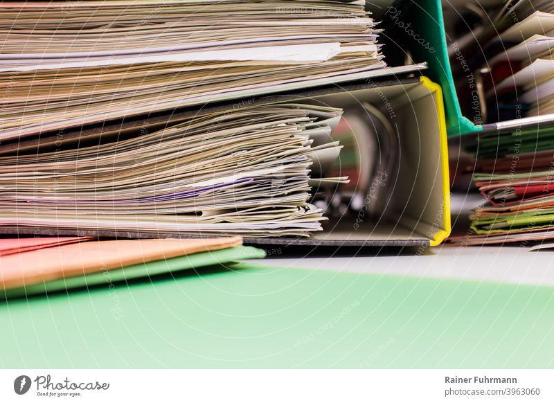 Ein unordentlicher Stapel aus Aktenordnern liegt auf einem Schreibtisch Büro Behörde Arbeitsplatz Arbeit & Erwerbstätigkeit Business Büroarbeit Nahaufnahme