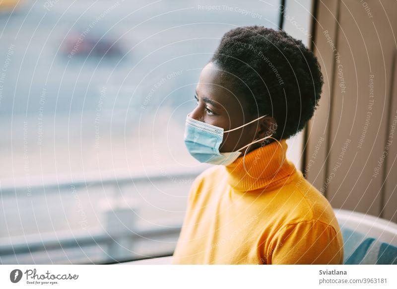 Dubai, VAE, November 2020 Eine junge Afrikanerin mit Schutzmaske fährt in einem Bus und schaut aus dem Fenster. Coronavirus, soziale Distanz. Seitenansicht Frau