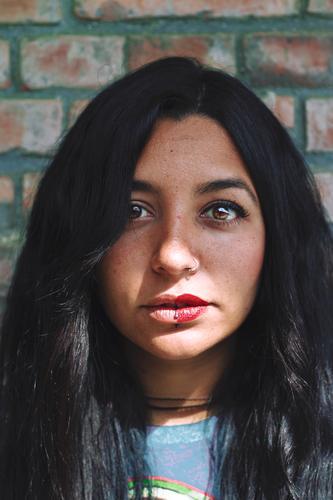 Eine junge schöne Frau mit Künstler-Make-up schaut in die Kamera zusammenstellen Junge Frau Aussehen Auge Lippen Licht hell