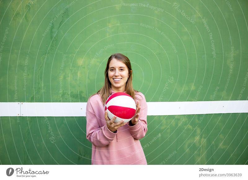 junge langhaarige Frau hält einen Basketball gegen grüne Wand Sport Person Fitness Training Athlet Ball Beteiligung Mädchen Spieler Übung Gesundheit Lifestyle