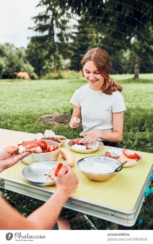 Familie beim Frühstück im Freien auf dem Campingplatz in den Sommerferien authentisch wirklich Banane gekochtes Fleisch langsames Leben Tischdecken im Freien