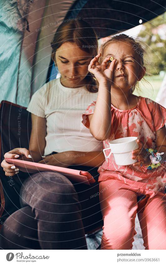 Schwestern verbringen Zeit in einem Zelt auf dem Campingplatz. Kinder mit Tablet spielen Spiele online während der Sommerferien Spielen Mädchen Geschwister
