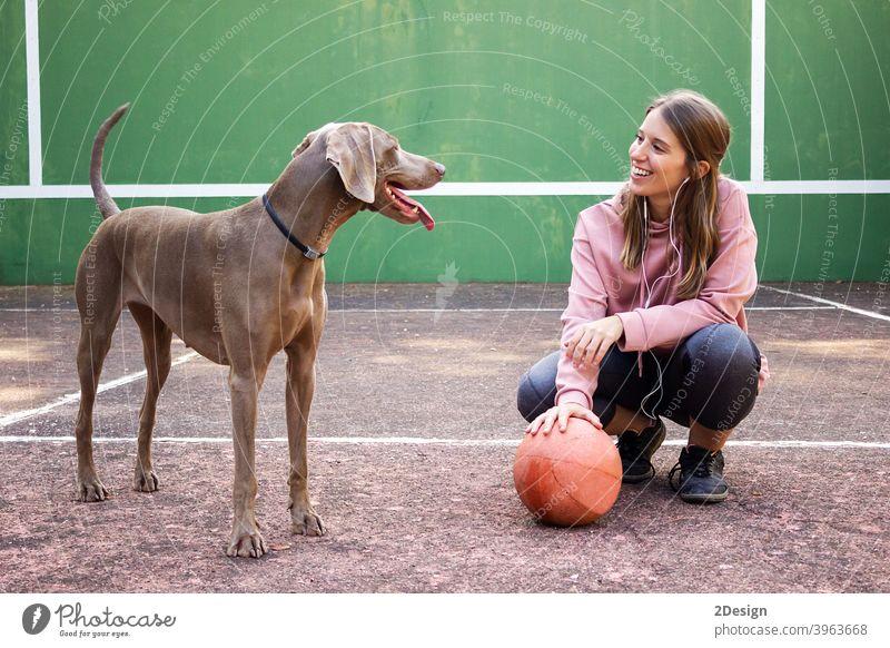 Junge Frau hält Ball posiert mit ihrem Hund Sport Person Basketball Beteiligung Mädchen Spieler Haustier Übung jung Gesundheit Lifestyle passen Körper Glück