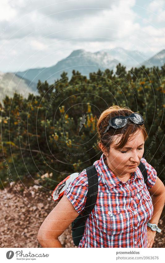 Frau mit Rucksack Wandern in einem Gebirge, aktiv verbringen Sommerurlaub, mit Pause nach dem Gehen auf einem Hügel Aktivität Abenteuer Freiheit grün Gesundheit