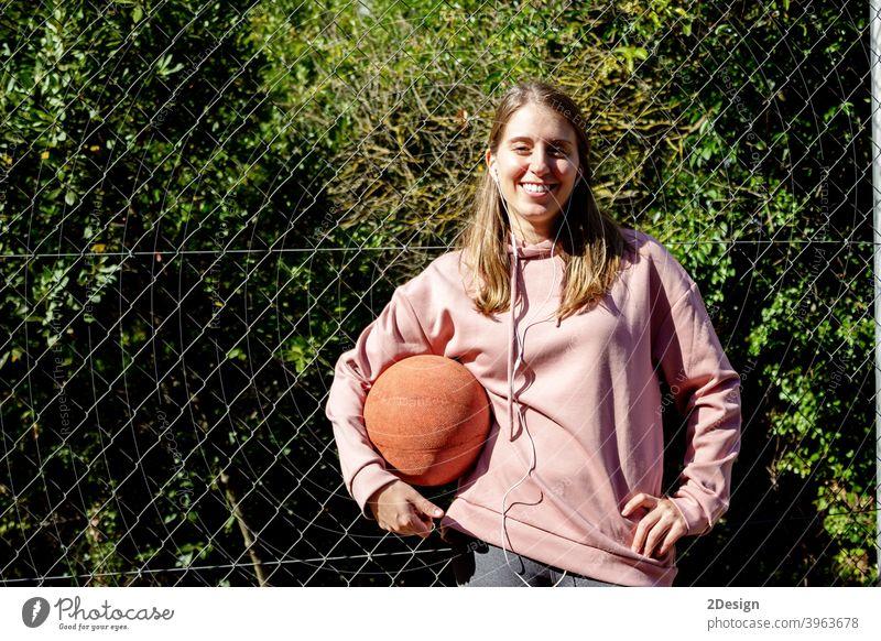 junge langhaarige Frau hält einen Basketball Sport Person Fitness Training Athlet Ball Beteiligung Mädchen Spieler Übung Gesundheit Lifestyle passen Körper