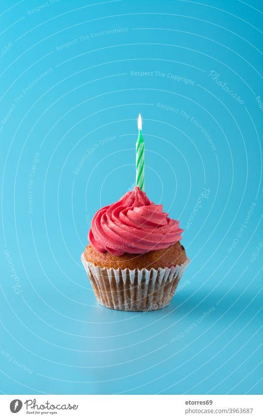 Rosa Geburtstag Cupcake auf blauem Hintergrund Bäckerei Buttercreme Kuchen Kerze feiern Konzept cremig dekoriert lecker Dessert Lebensmittel Zuckerguss