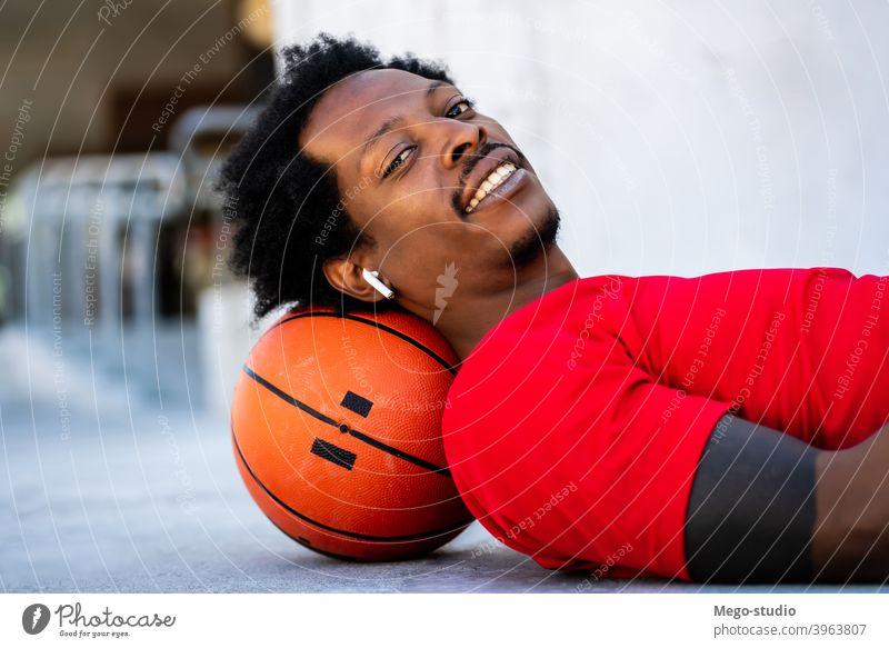 Afro-Athlet Mann auf dem Boden liegend nach dem Training. Sport Basketball Ball urban sportlich im Freien Stehen genießen Ausdruck aktiv Hand Übung Erholung