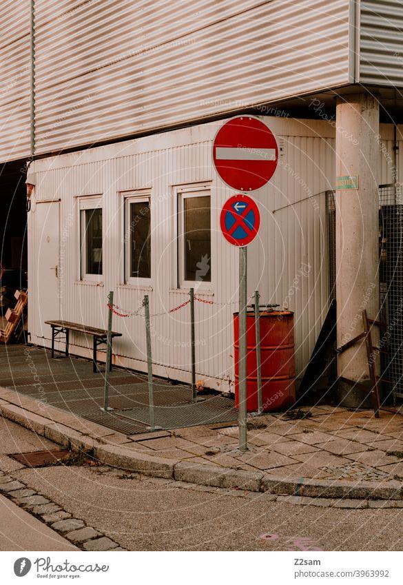 Halteverbotsschid in Industrieumgebung Straßenfotografie schild Fußgänger industriegebiet Schilder zeichen mülltonne beton Stadt urban warme farben sonnig