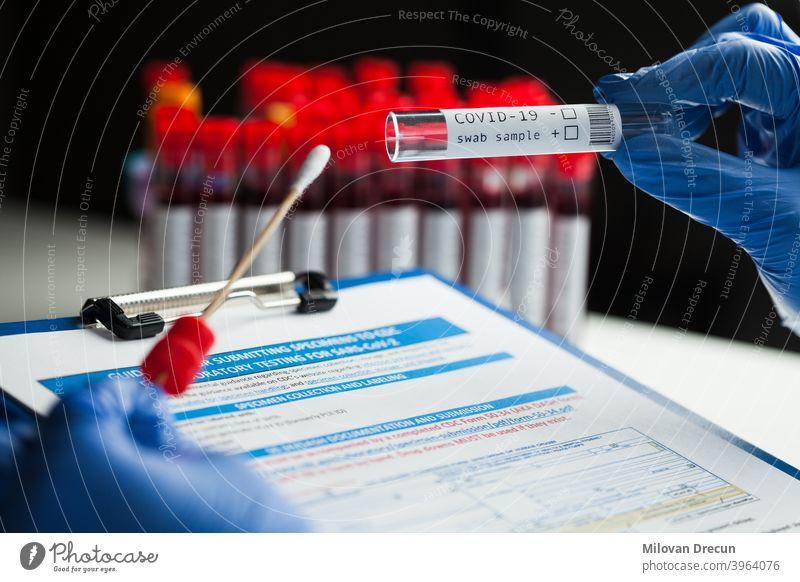 rt-PCR COVID-19 Viruserkrankung diagnostischer Test, Labortechniker mit blauen Schutzhandschuhen, der ein Reagenzglas mit einem Tupferstab hält, Tupferproben-Ausrüstungssatz & CDC-Formular mit Richtlinien zur Einreichung von Proben