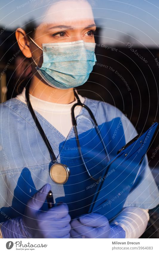 Arzt schaut durch das Fenster blau Pflege Klinik Korona Coronavirus COVID Krankheit Notfall Seuche erschöpft Gesicht Angst Frau Frontlinie Frustration Glas
